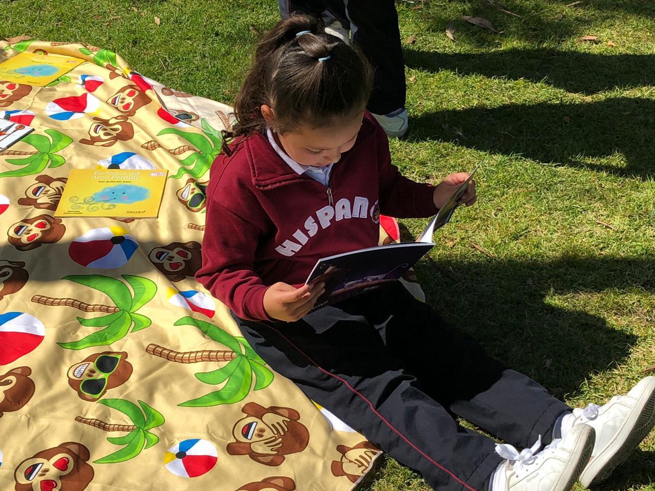 Niña en sentada en el pasto leyendo del Colegio Bilingue Hispanoamericano Conde Ansurez